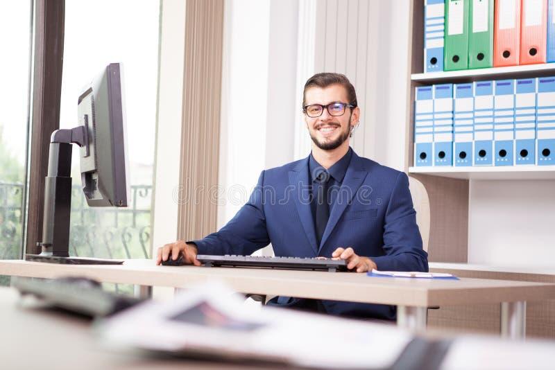Zakenman in kostuum die bij zijn computer naast een glaswind werken royalty-vrije stock afbeeldingen