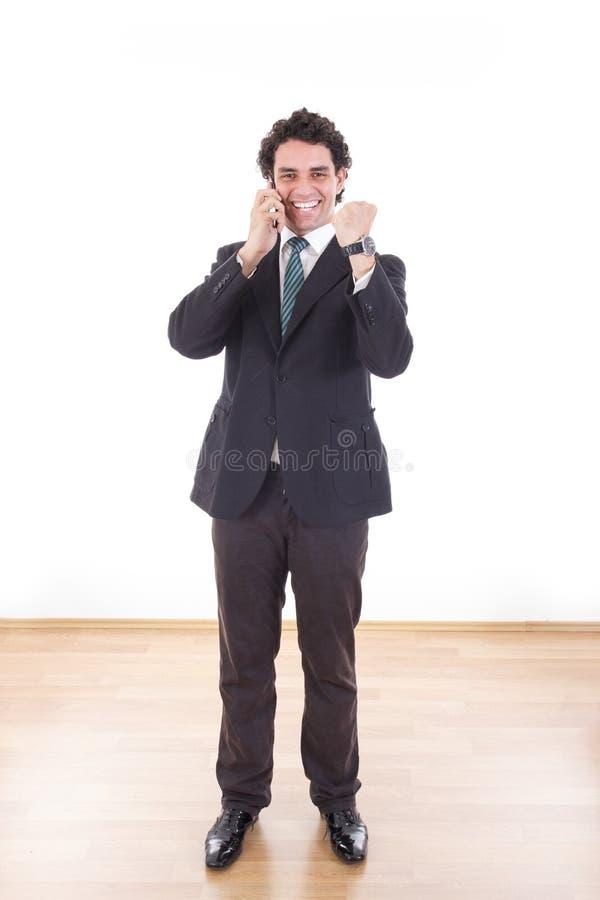 Zakenman in kostuum die met cel mobiele telefoon spreken met omhoog vuist stock afbeelding