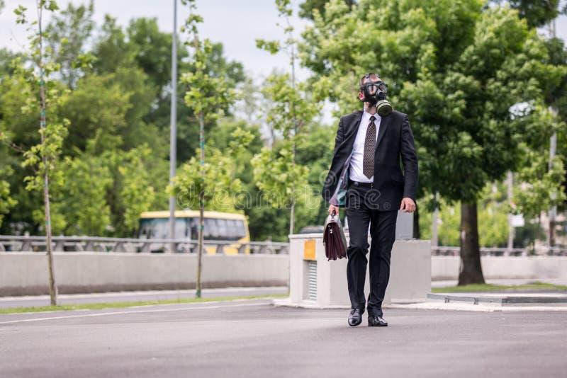 Zakenman lopen openlucht met aktentas die een gasmasker dragen royalty-vrije stock afbeelding