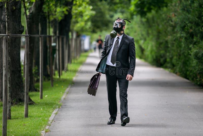 Zakenman lopen openlucht met aktentas die een gasmasker dragen stock fotografie