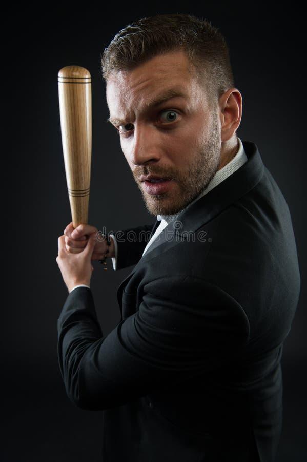 Zakenman of mens in formeel kostuum op donkere achtergrond Mens bij het strikte gezicht stellen met houten knuppel De mens met va royalty-vrije stock afbeelding