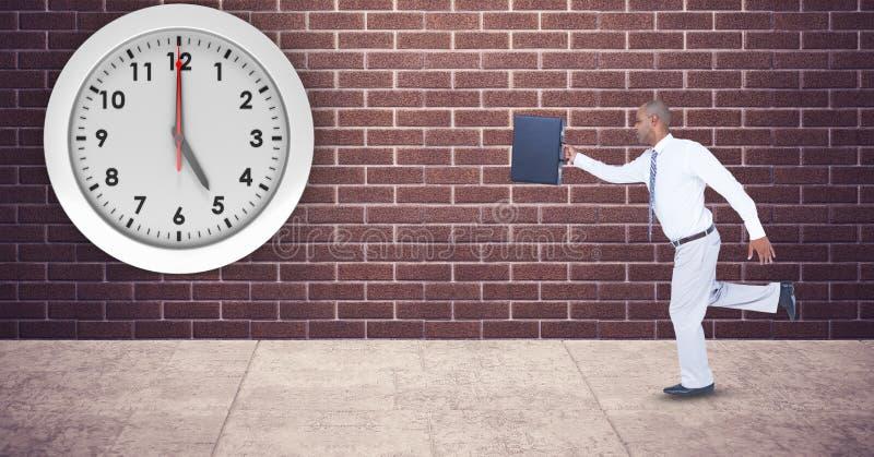 Zakenman met aktentas die laat met klok opgezet op muur lopen royalty-vrije stock fotografie