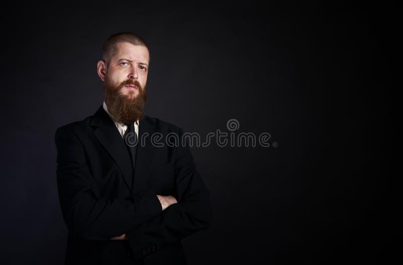 Zakenman met baard op zwarte achtergrond in zwarte kostuumplaats voor exemplaar-deeg royalty-vrije stock afbeeldingen