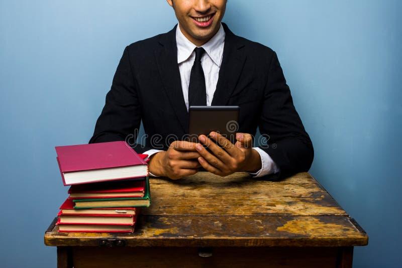 Zakenman met boeken en e-lezer stock fotografie