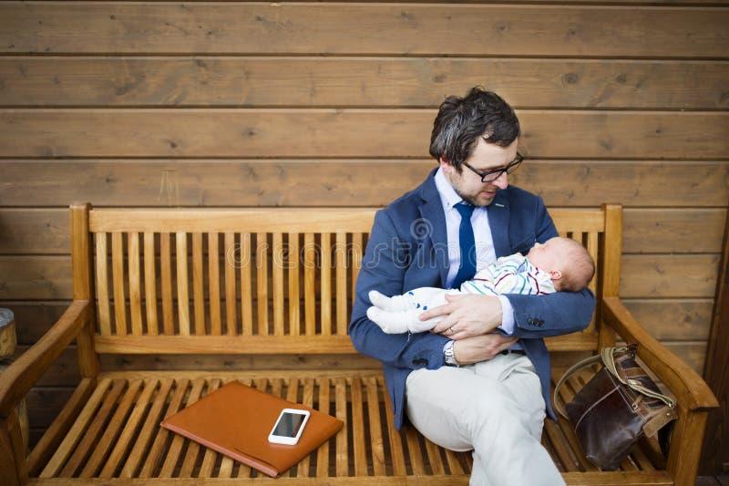 Zakenman met de zitting van de babydochter op voorportiek royalty-vrije stock fotografie