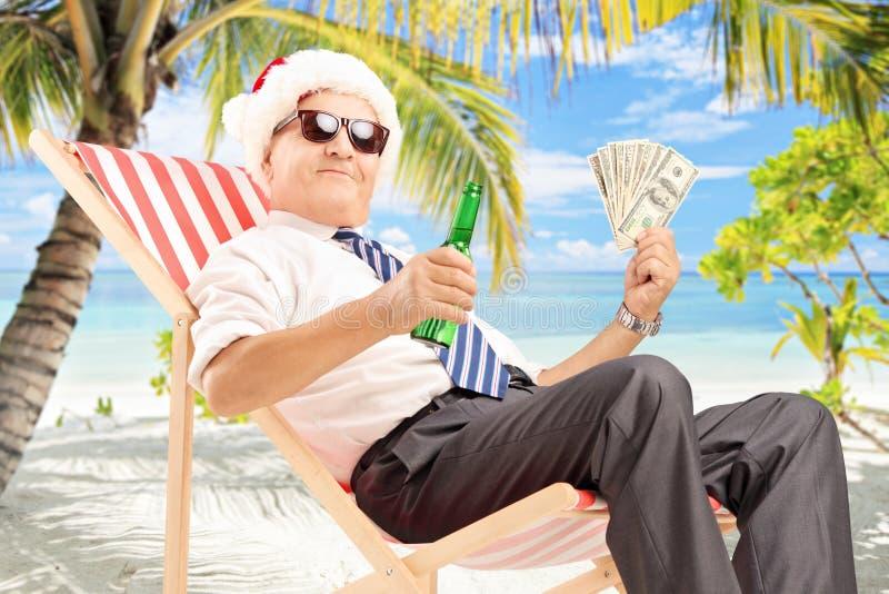 Zakenman met de zitting van de santahoed op stoel en holdingsdollars royalty-vrije stock afbeeldingen