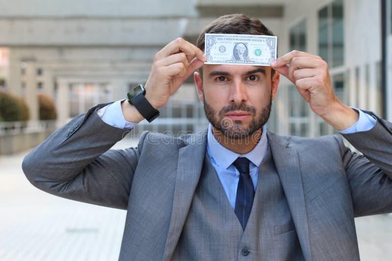 Zakenman met dollar op zijn voorhoofd royalty-vrije stock afbeelding