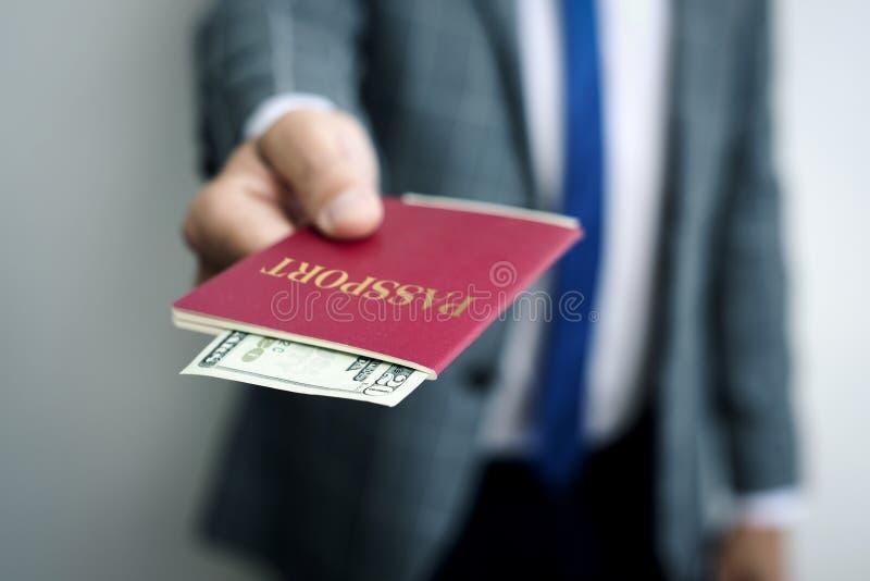 Zakenman met 20 dollars in zijn paspoort stock fotografie