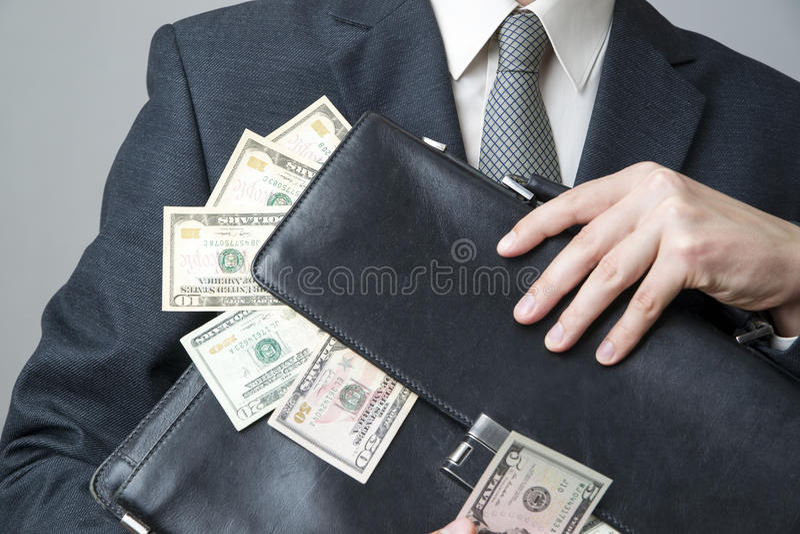 Zakenman met een aktentashoogtepunt van geld in de handen van stock fotografie