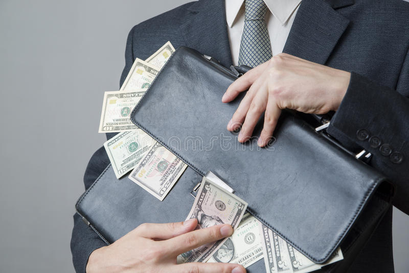 Zakenman met een aktentashoogtepunt van geld in de handen van stock afbeelding