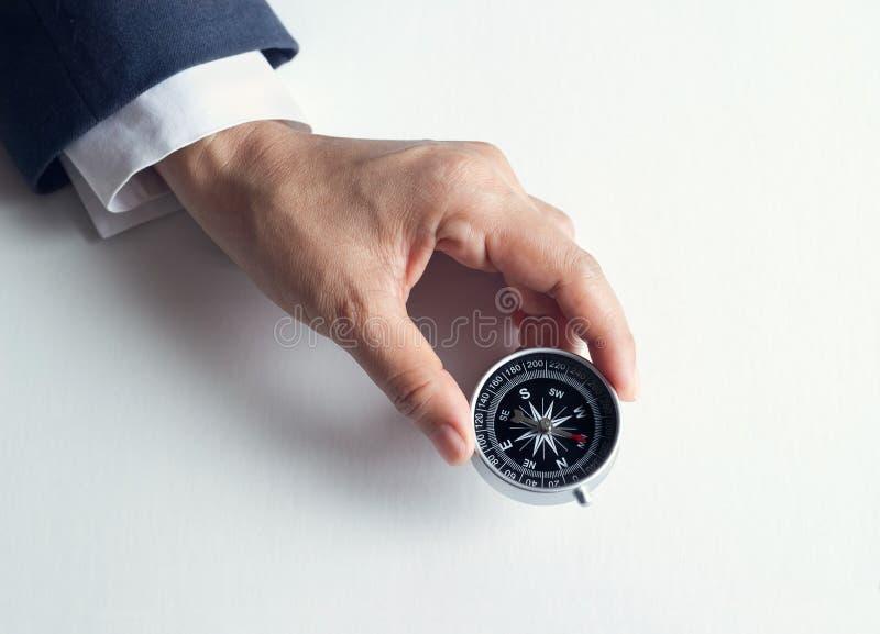Zakenman met een kompasholding ter beschikking op document achtergrond stock foto's
