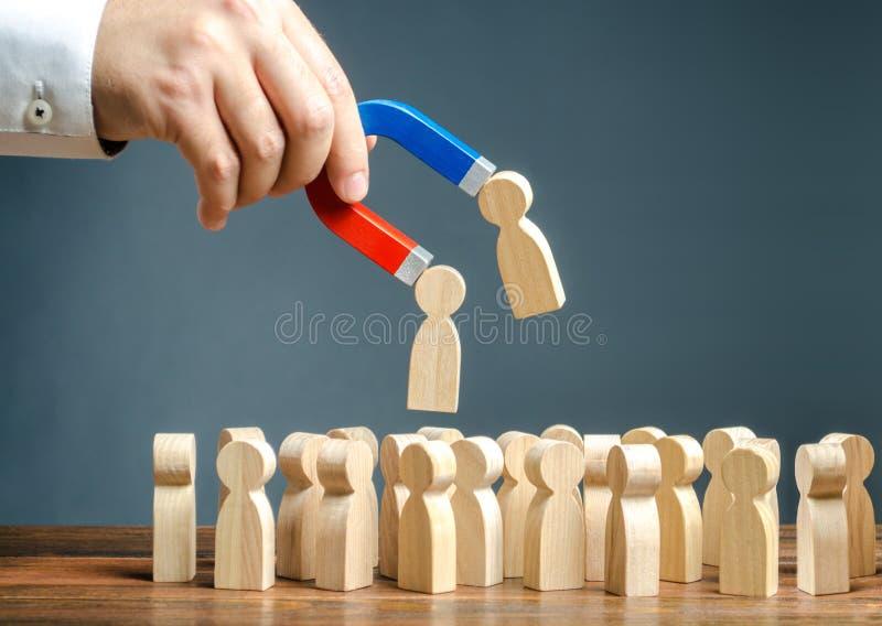 Zakenman met een magneet die houten cijfers van mensen van de menigte trekken Het aanwerven van nieuwe arbeiders, koppensnellers stock foto