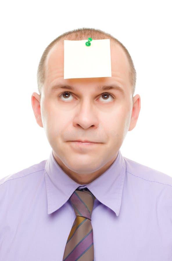 Zakenman met een nota die op zijn hoofd wordt gespeld royalty-vrije stock fotografie