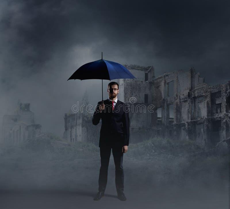 Zakenman met een paraplu op stadsruïnes royalty-vrije stock afbeeldingen