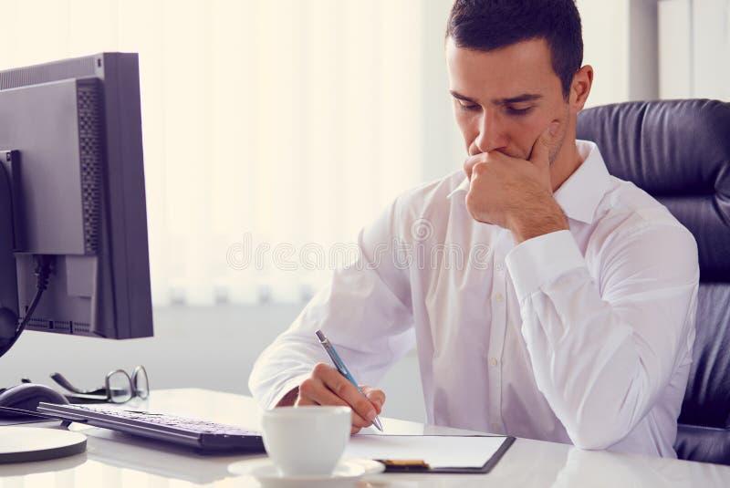 Zakenman met een pen in het bureau stock foto
