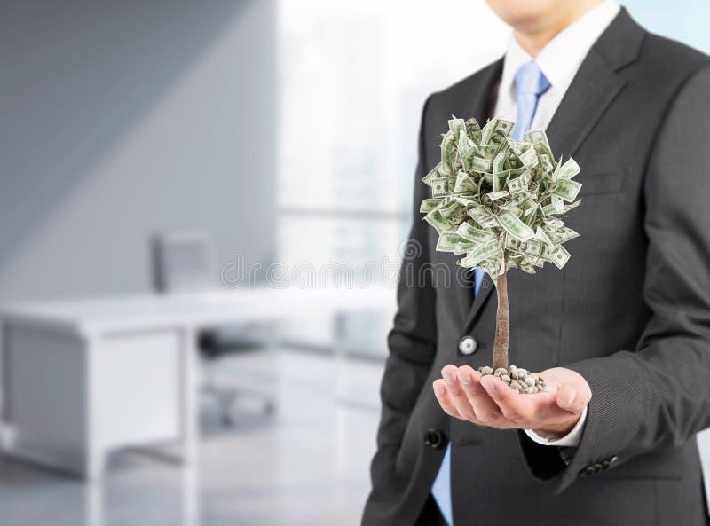 Zakenman met een uiterst kleine dollarboom, bureau het 3d teruggeven stock afbeelding
