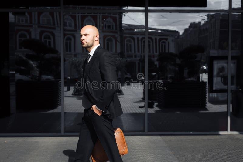 Zakenman met een zak dichtbij het bureau royalty-vrije stock afbeelding