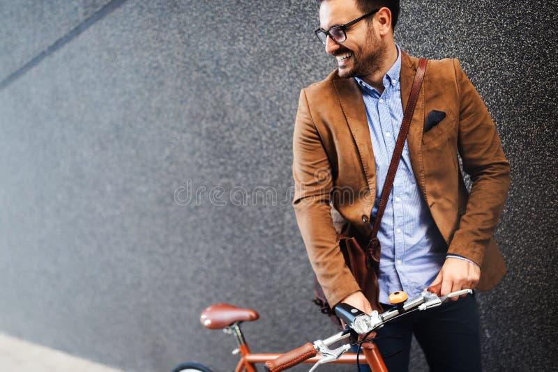 Zakenman met fiets om aan stedelijke straat in stad te werken Vervoer en gezond levensstijlconcept stock fotografie