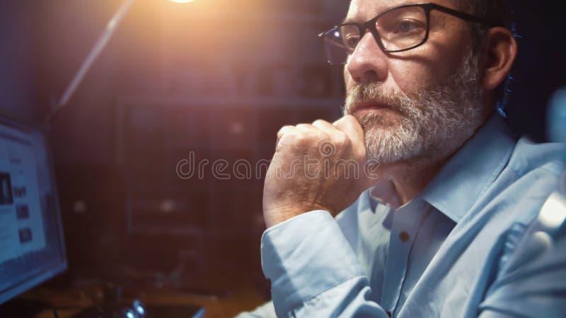 Zakenman met glazen werken geconcentreerd in bureau bij nacht stock fotografie