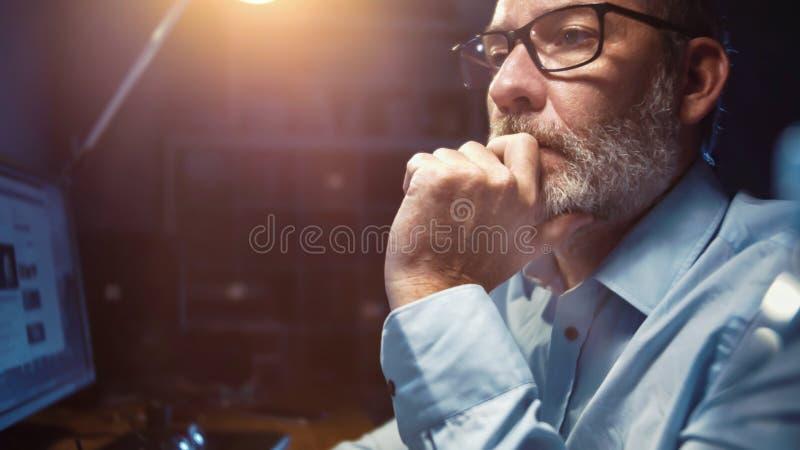 Zakenman met glazen werken geconcentreerd in bureau bij nacht stock foto's