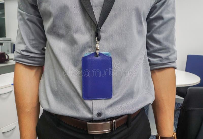 Zakenman met grijs overhemd en halsbedrijfkenteken in bureau royalty-vrije stock fotografie