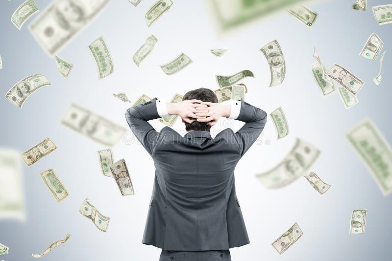 Zakenman met handen achter hoofd in geldstroom stock afbeeldingen