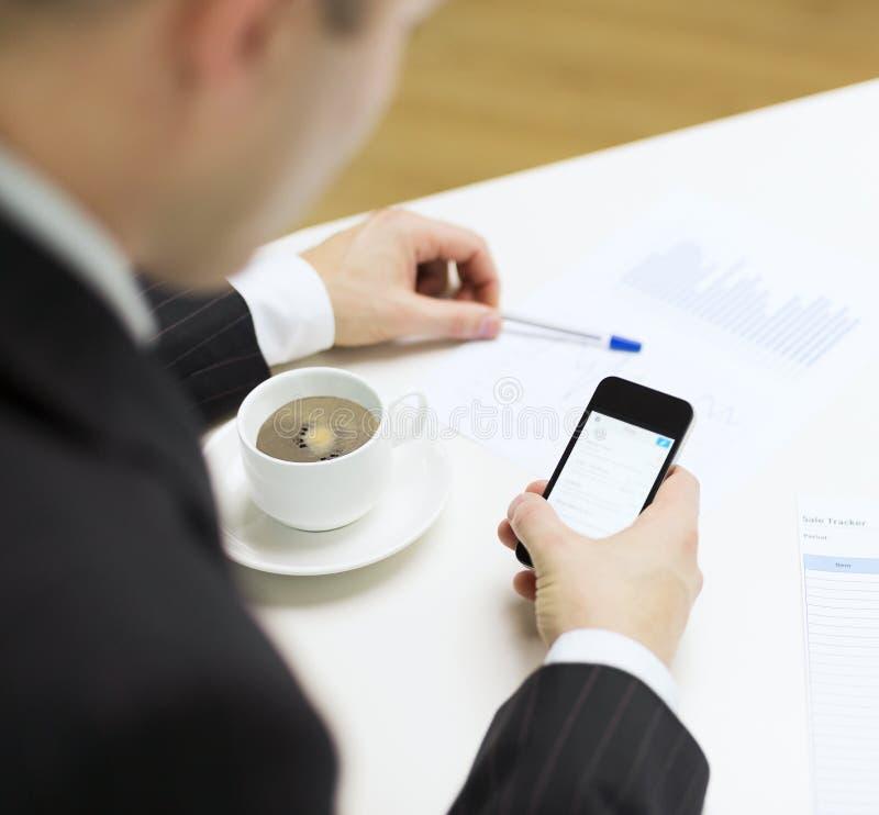 Zakenman met het nieuws van de smartphonelezing stock fotografie