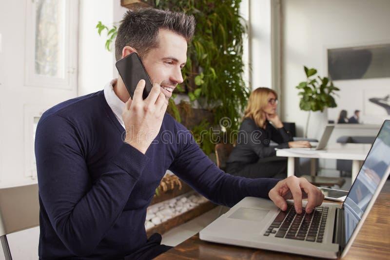 Zakenman met het telefoneren van en het werken aan laptop terwijl het zitten in het bureau royalty-vrije stock afbeelding