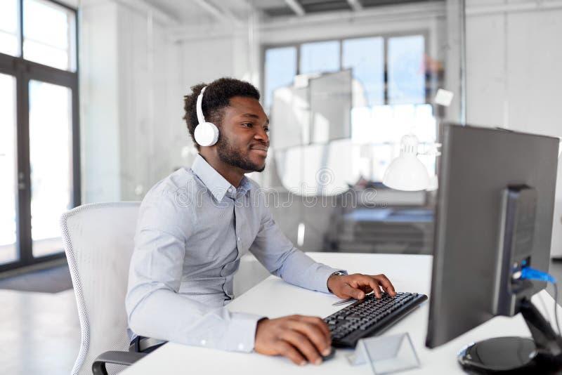 Zakenman met hoofdtelefoons en computer op kantoor stock fotografie
