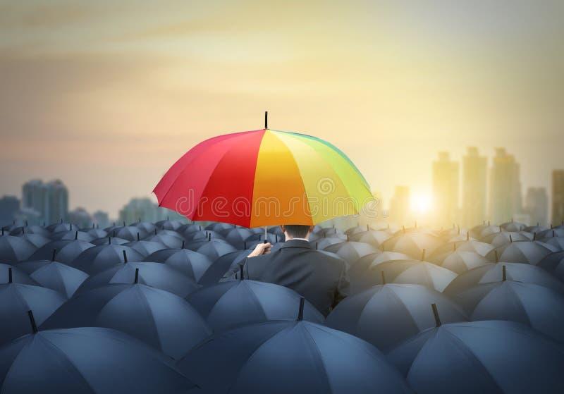 Zakenman met kleurrijke unieke regenboogparaplu onder andere, stock foto's