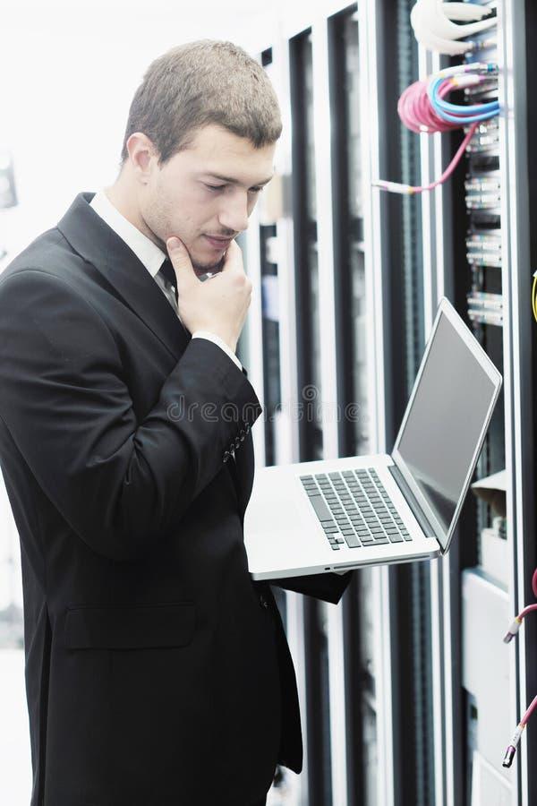 Zakenman met laptop in de ruimte van de netwerkserver stock foto