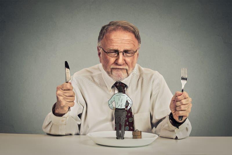 Zakenman met mes en vork die zijn werknemer op een plaat bekijken stock fotografie