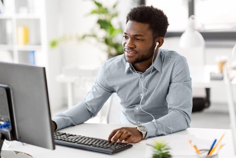 Zakenman met oortelefoons en computer op kantoor stock afbeeldingen