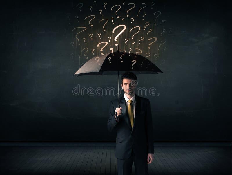 Zakenman met paraplu en heel wat getrokken vraagtekens royalty-vrije stock fotografie