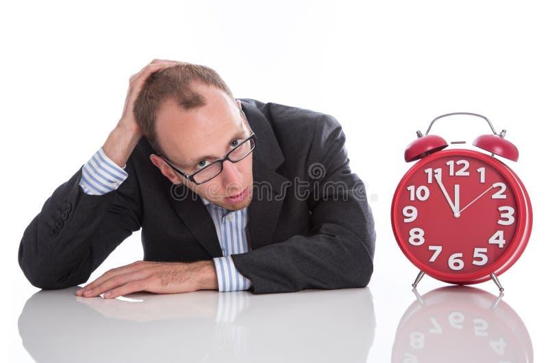 Zakenman met rode die klok wordt op witte backgrou wordt geïsoleerd overgewerkt die stock afbeelding