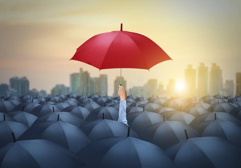 Zakenman met rode paraplu onder andere, uniek verschillend concept stock afbeeldingen