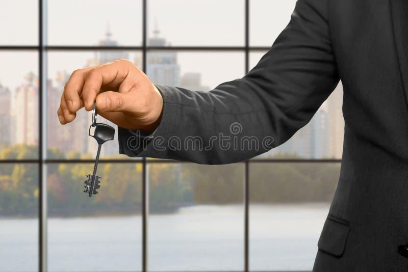 Zakenman met sleutel naast venster stock afbeelding