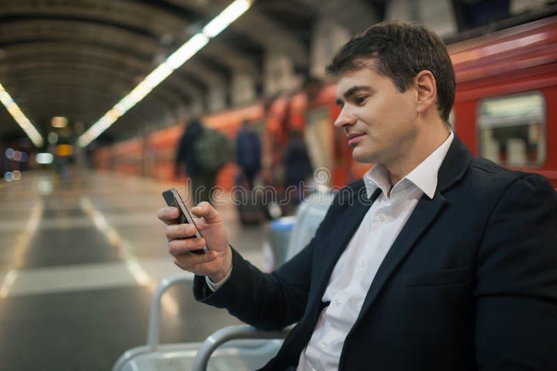 Zakenman met smartphone in metro stock afbeelding
