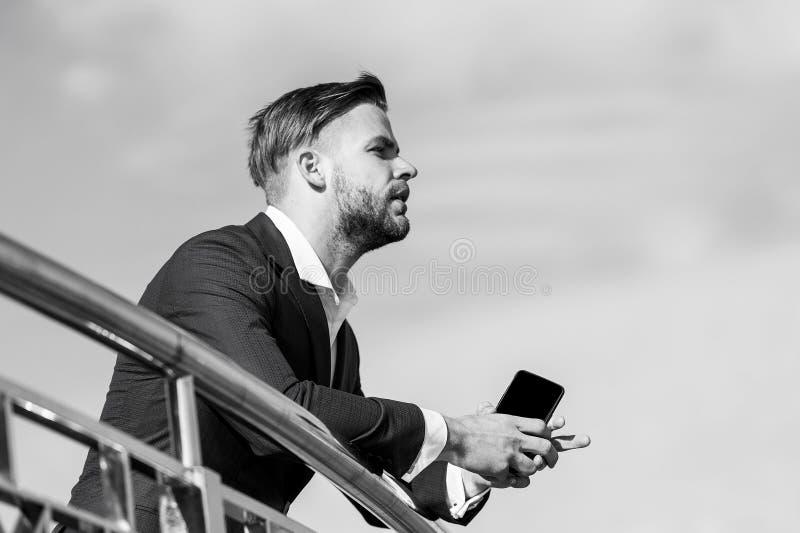 Zakenman met smartphone op terras op blauwe hemel, bedrijfsmededeling royalty-vrije stock foto's