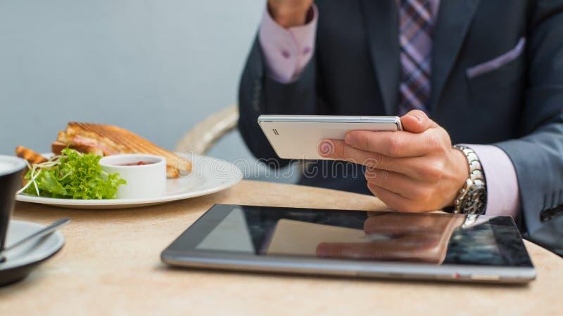 Zakenman met tablet en smartphone tijdens ontbijt. stock fotografie