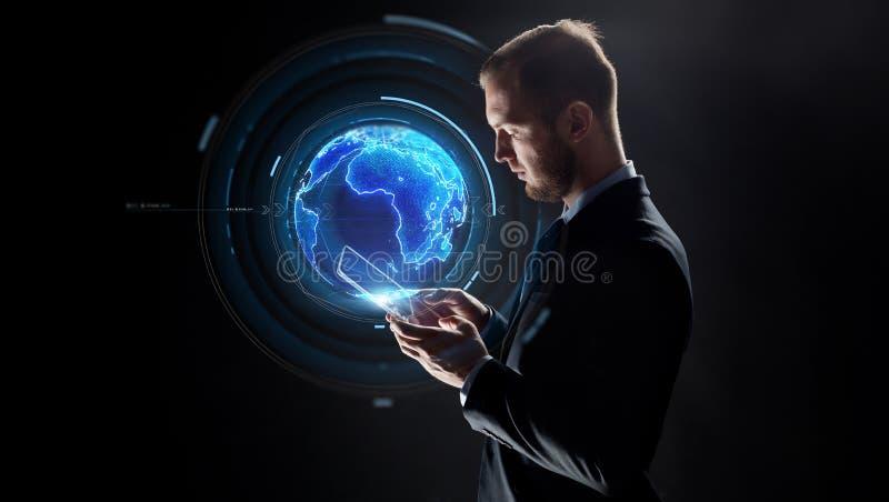 Zakenman met tabletpc en aardehologram royalty-vrije stock afbeelding