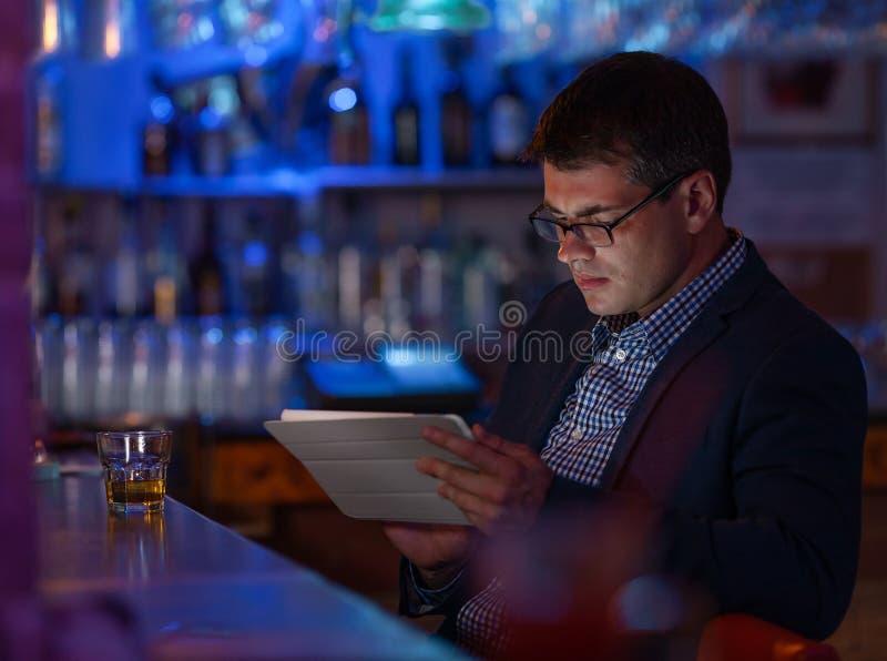 Zakenman met tabletpc en wisky bij de barteller stock foto's