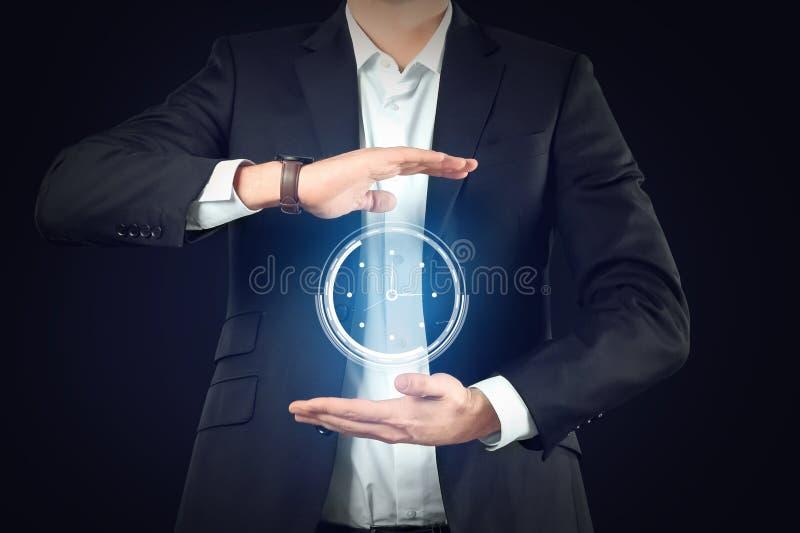 Zakenman met virtuele klok op donkere achtergrond Het Concept van het tijdbeheer stock afbeelding