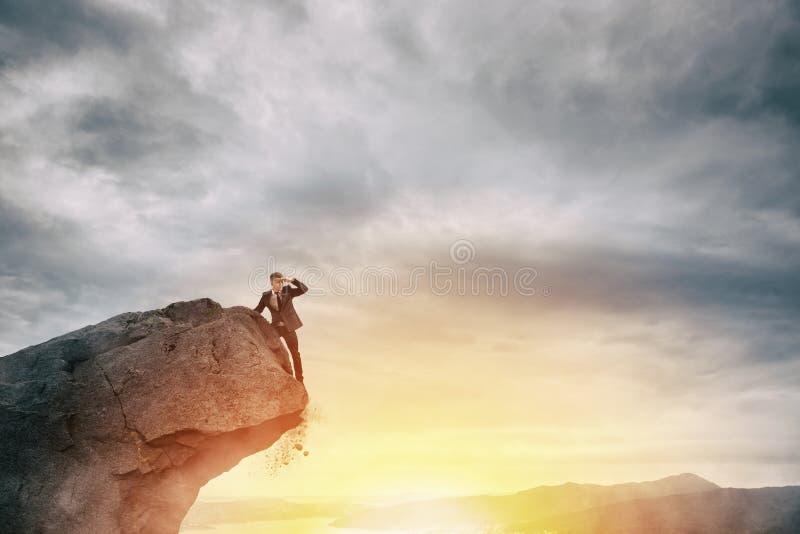Zakenman op de piek van een berg om nieuwe zaken te vinden stock foto