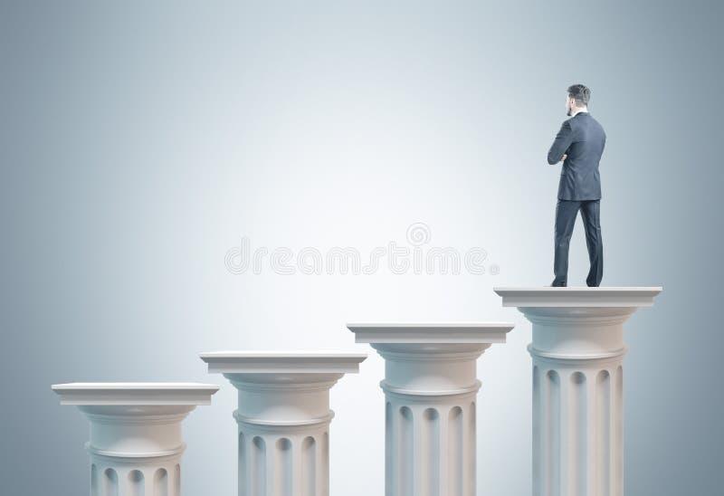 Zakenman op een kolom, grijze achtergrond stock foto