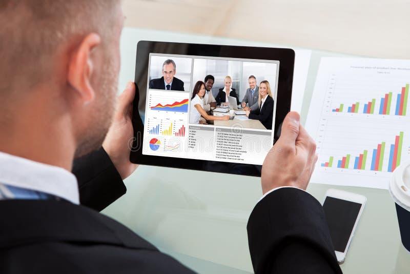 Zakenman op een video of conferentievraag op zijn tablet royalty-vrije stock fotografie