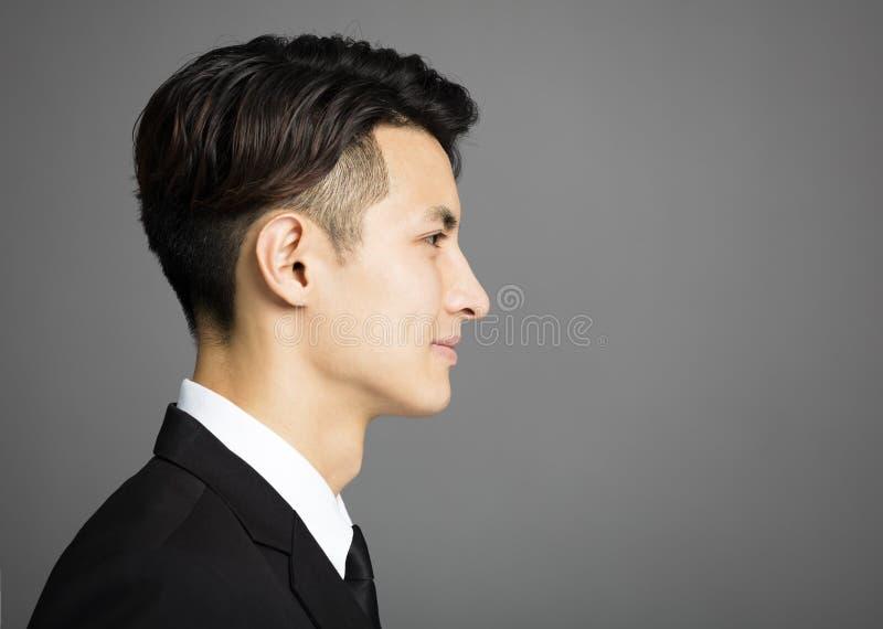 Zakenman op grijze achtergrond wordt geïsoleerd die stock fotografie
