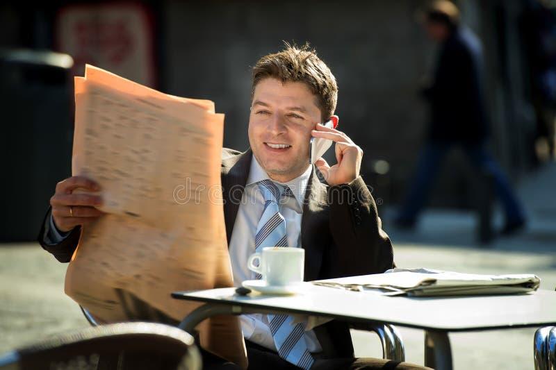 Zakenman op straatbar die het nieuws hebben die van de de lezingskrant van de ontbijtkoffie op mobiele telefoon spreken royalty-vrije stock foto