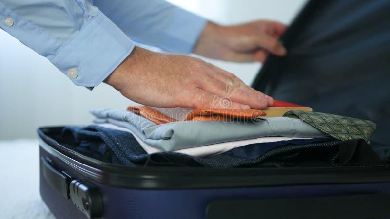 Zakenman Prepare een Koffer met Kleren en Gezet binnen een Lezingsboek stock afbeeldingen