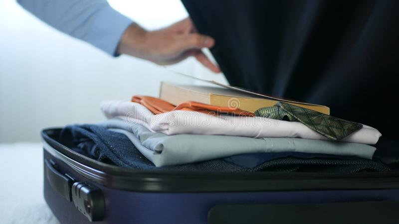 Zakenman Prepare een Koffer met Kleren en Gezet binnen een Lezingsboek stock foto's